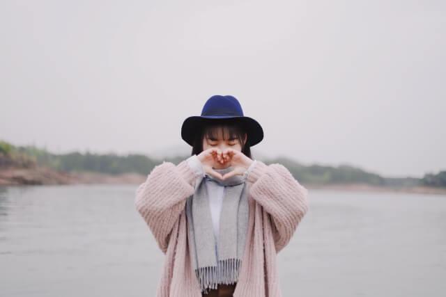 ピンクのカーディガンに青いハットを被って両手でハートマークを作っている若い女性