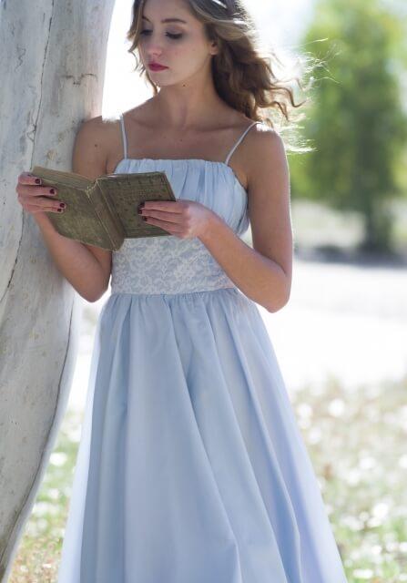 木の隣で本を読んでいるキャミソールワンピースを着ている女性