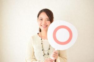 丸が描かれたフリップを持つ笑顔の女性