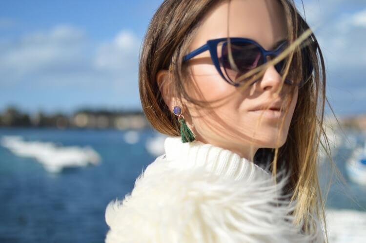 白いニットを着たサングラスの女性