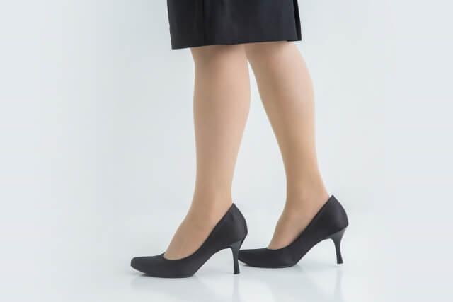 スーツに黒いパンプスを履いている女性の脚